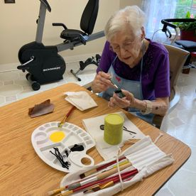 old woman painting an object